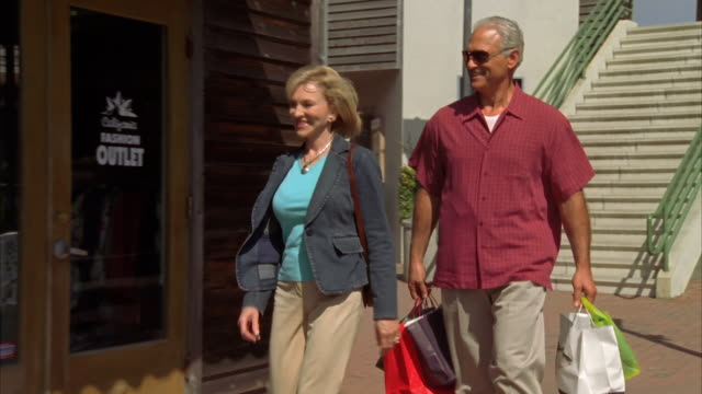 MS, DS, Mature couple with shopping bags walking on street, Morro Bay, California, USA,