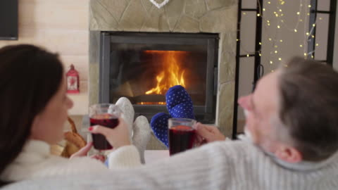 mature couple with tea relaxing by the fireplace/ krynica/ poland - erwachsene person stock-videos und b-roll-filmmaterial