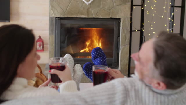 mature couple with tea relaxing by the fireplace/ krynica/ poland - kamin stock-videos und b-roll-filmmaterial