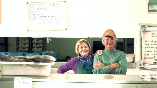 Mature couple working fish market