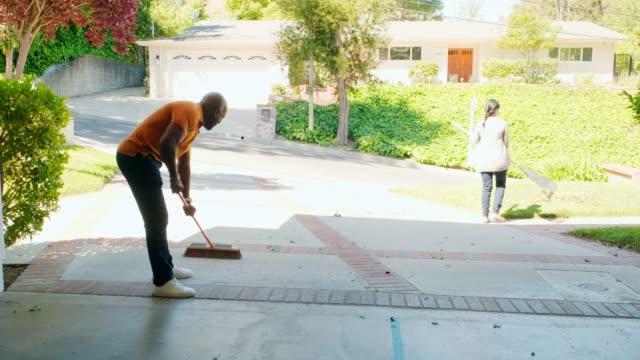 vídeos y material grabado en eventos de stock de pareja madura trabajando en frontyard de su casa - barrer