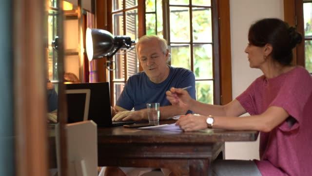 vídeos y material grabado en eventos de stock de madura pareja trabajando juntos en el hogar - financial bill