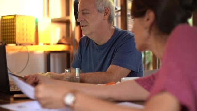 vídeos de stock e filmes b-roll de mature couple working together at home - plano documento