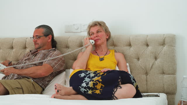 reife paare ruhen auf einem bett in einem hotelzimmer, die frau ruft service mit dem zimmer telefon. - quarantäne stock-videos und b-roll-filmmaterial