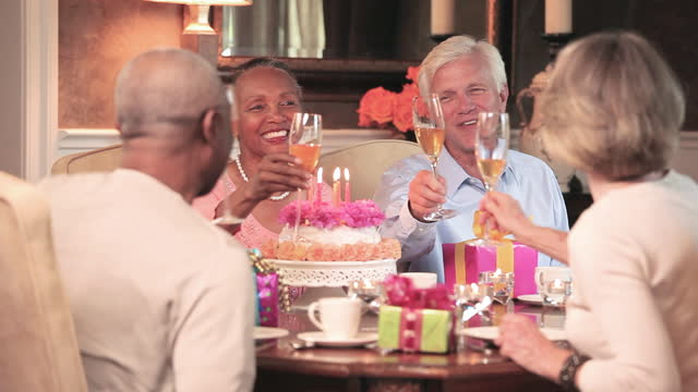 vidéos et rushes de mature couples toasting champagne flutes and woman blowing out candles on birthday cake - anniversaire