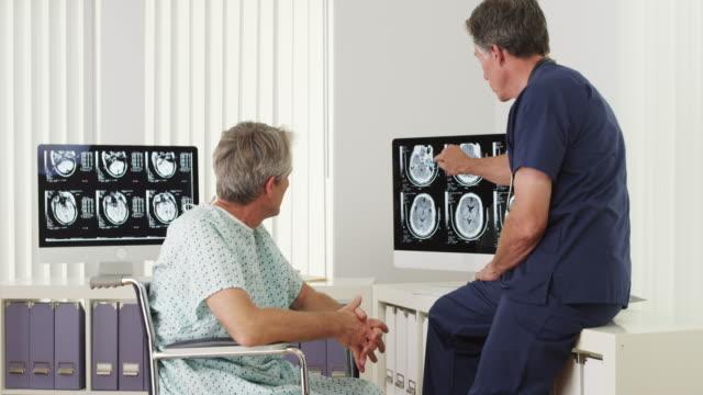 vídeos y material grabado en eventos de stock de mature doctor explaining xrays to disabled elderly patient - fiabilidad