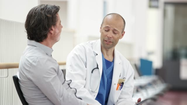 mature doctor showing digital tablet to patient - mature men stock videos & royalty-free footage