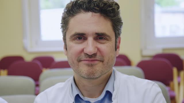 vidéos et rushes de docteur mûr s'asseyant sur l'auditorium d'hôpital - chirurgien