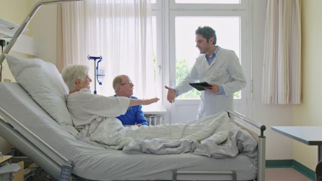 定期検診のために病院の病棟を訪問する成熟した医師 - 挨拶点の映像素材/bロール