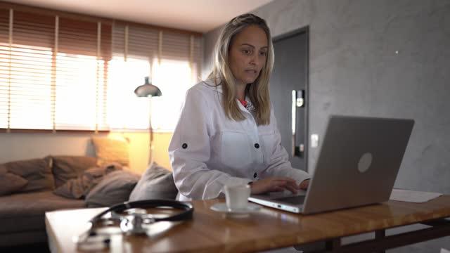 reife arzt arbeiten mit laptop zu hause - ärztin stock-videos und b-roll-filmmaterial