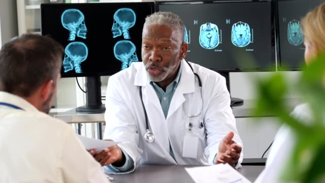 mature doctors speaks with several other doctors - medical x ray stock videos & royalty-free footage