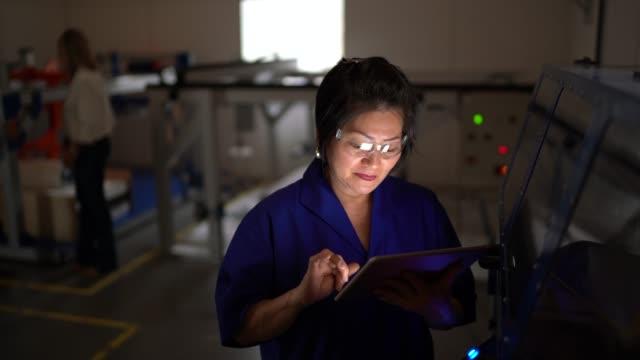 vidéos et rushes de employé mûr travaillant et utilisant la tablette aux machines dans l'industrie - technicien de maintenance