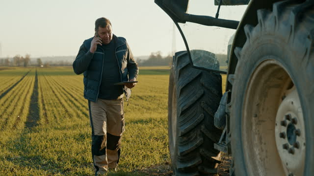 slo mo mature farmer having a call while looking at a digital tablet next to a tractor - farmer stock videos & royalty-free footage