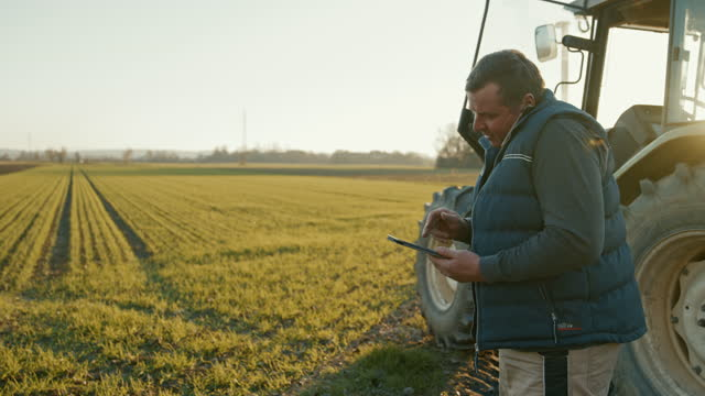 slo mo mature farmer having a call while using a digital tablet on the field - 1 minute or greater stock videos & royalty-free footage