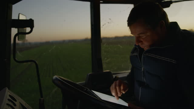 slo mo mature farmer using a digital tablet inside of his tractor - one mature man only stock videos & royalty-free footage