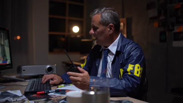 mature fbi agent using computer at work - jacket stock videos & royalty-free footage