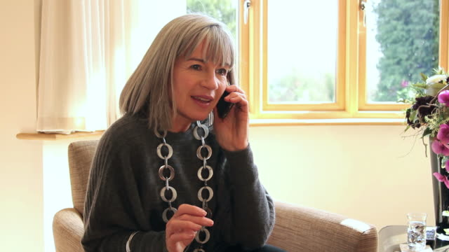 Mature female answering phone call at home