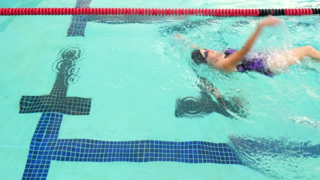 MS HA Mature female athlete swimming backstroke in outdoor pool during early morning workout