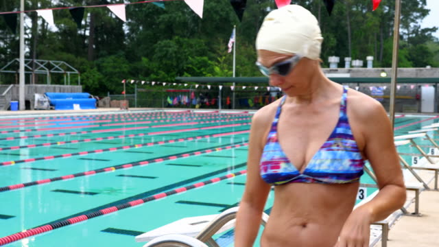 ms ts td mature female athlete walking on outdoor pool deck before starting early morning workout - swimming cap stock videos and b-roll footage