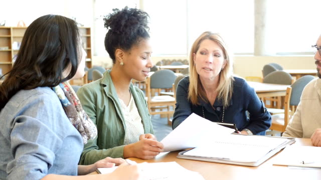 Mature female college professor meeting with diverse adult students