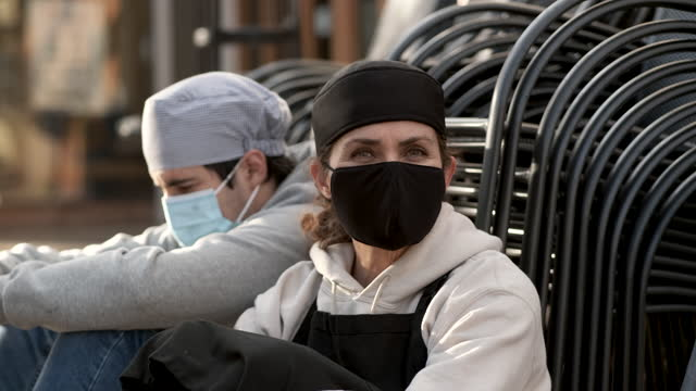 mature female cook posing with a male young coworker wearing both protective face masks sitting on the floor outside the restaurant they work - unemployment stock videos & royalty-free footage