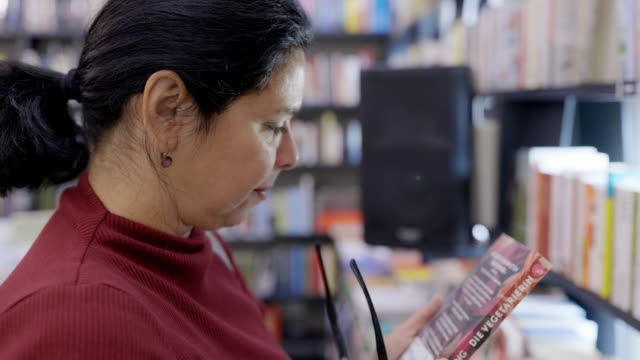 mature female customer shopping books in a store - book shop stock videos & royalty-free footage