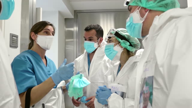 mature female doctor briefing colleagues at corridor for the day - rubber glove stock videos & royalty-free footage