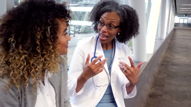 mature female doctor discusses something with young woman - medical sales representative stock videos & royalty-free footage