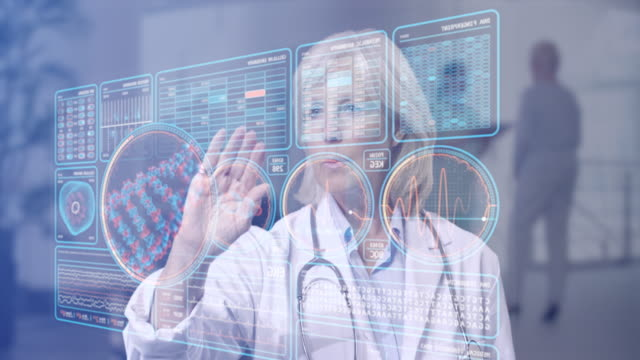 vídeos y material grabado en eventos de stock de mature female doctor looking at futuristic medical charts at a high tech hospital - interactividad
