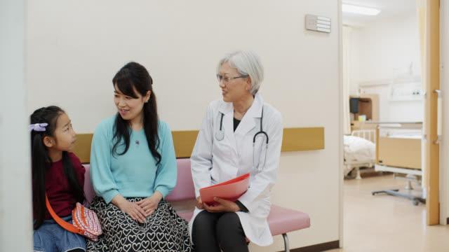 vidéos et rushes de femme mature médecin parlant avec des patients - salle d'attente