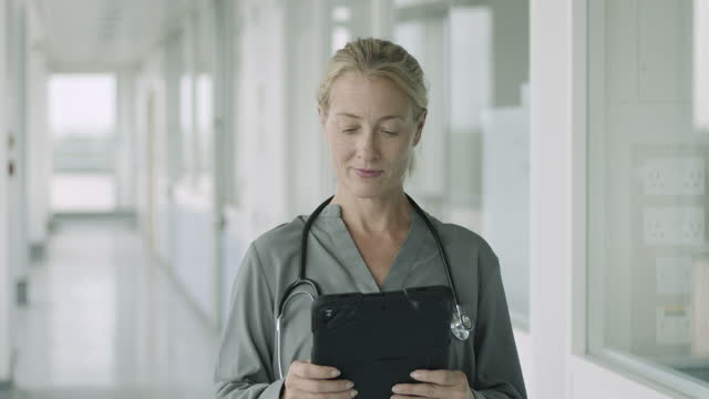 mature female doctor standing in modern hospital corridor working on digital tablet and looking out of window - blouse stock videos & royalty-free footage