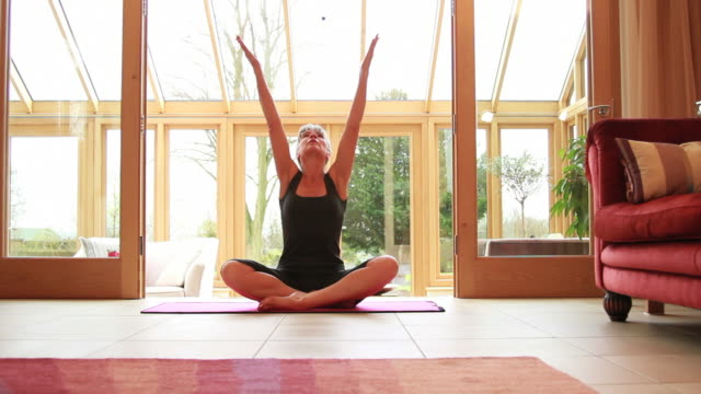 Mature female exercising yoga at home