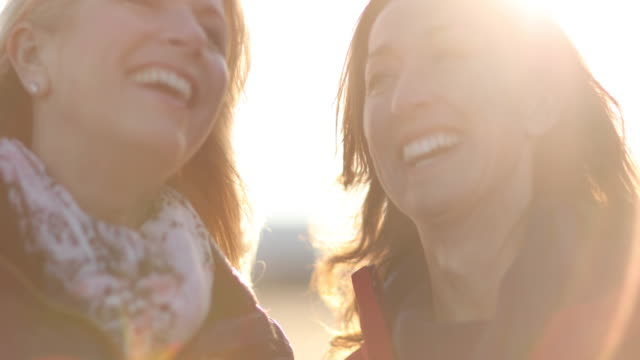 Mature female friends laughing outdoors