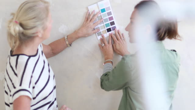 Mature female friends looking at colour card