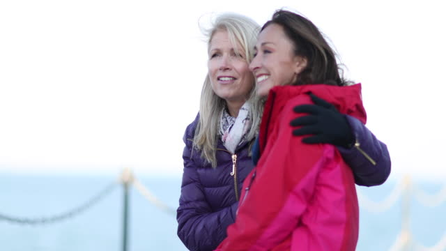Mature female friends looking out to sea