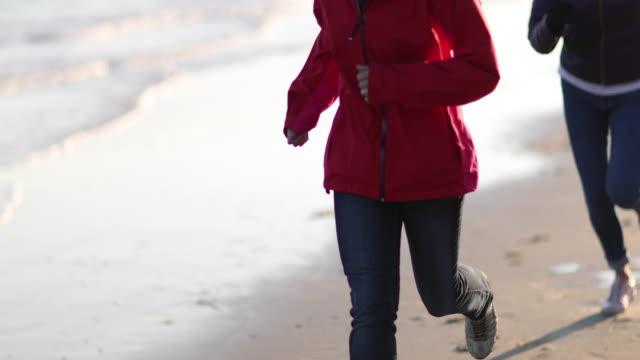 Mature female friends running outdoors