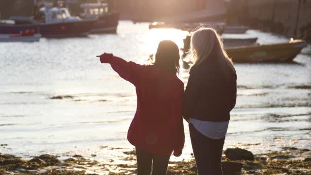 Mature female friends talking in harbour