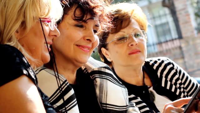 Mature female friends using digital tablet