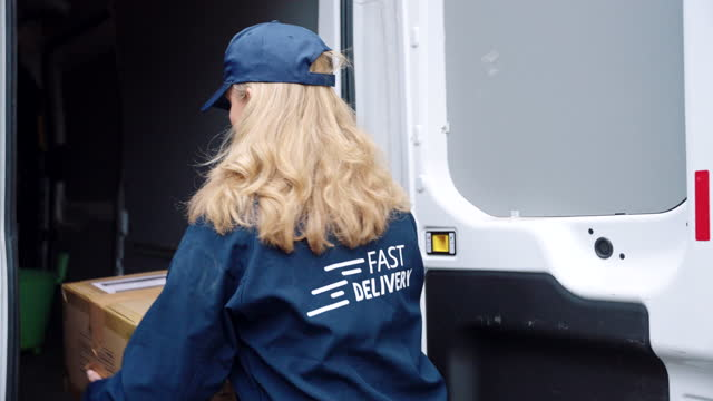 mature female gig driver with package for residential delivery - van stock videos & royalty-free footage