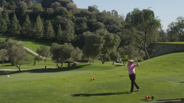 ha ws mature female golfer teeing off, exiting frame right, red r3d 4k - golf glove stock videos and b-roll footage