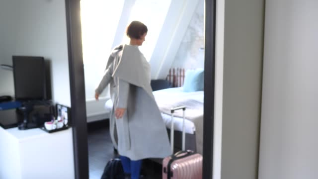 vídeos y material grabado en eventos de stock de mature female guest entering bedroom and removing overcoat seen through doorway at hotel - huésped