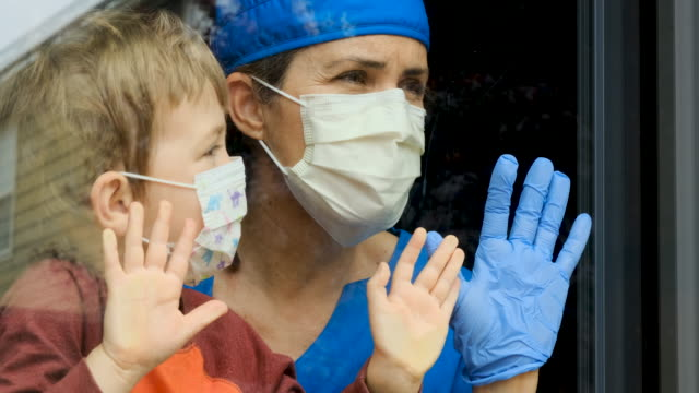 vídeos de stock e filmes b-roll de mature female healthcare worker posing with her son, both with protective masks, very sad looking through window worried about covid-19 lockdown - epidemia