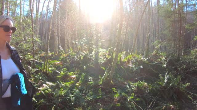 mogen kvinnlig vandrare följer skogsstigen - 55 59 år bildbanksvideor och videomaterial från bakom kulisserna