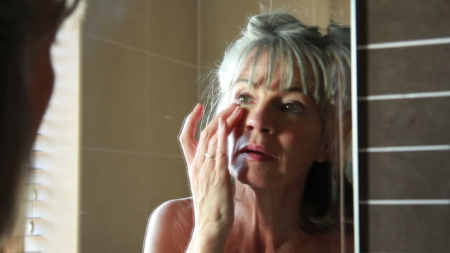 mature female in bathroom, applying eye cream - bra stock videos & royalty-free footage