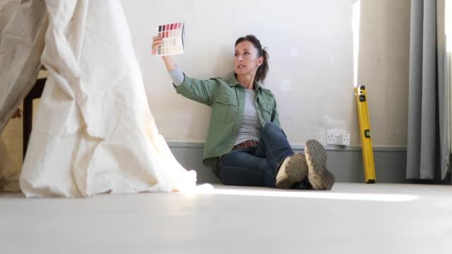 mature female looking at colour card - 床に座る点の映像素材/bロール