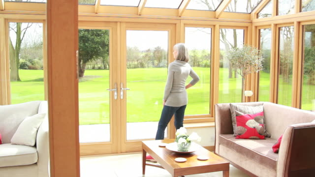 mature female looking out of window at home - viewpoint stock videos and b-roll footage