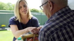 Mature Female Neighbor Helping Senior Man With Shopping