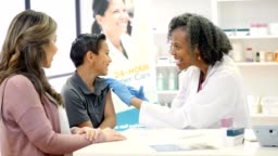 Mature female pharmacist gives flu vaccine to elementary age patient