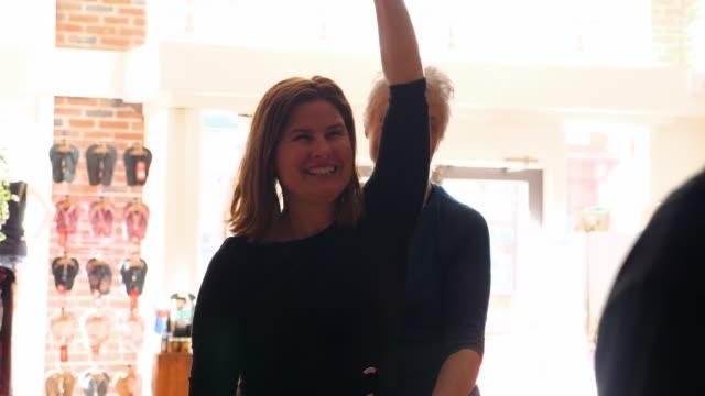 vídeos y material grabado en eventos de stock de ms mature female pilates instructor helping student on pilates chair during class in fitness studio - pilates