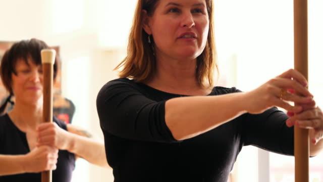vídeos y material grabado en eventos de stock de r/f mature female pilates instructor leading exercise during class in fitness studio - pilates
